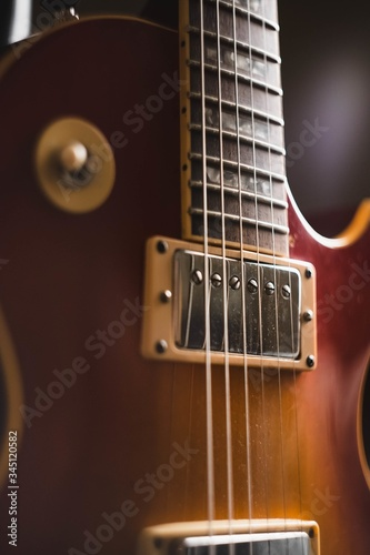 Closeup shot of the details of a brown guitar with a dark background