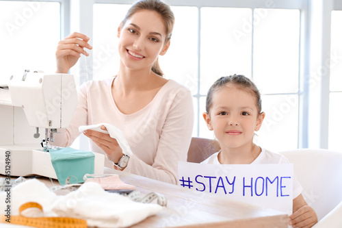 Fototapeta Little daughter with her mother sewing protective masks at home obraz