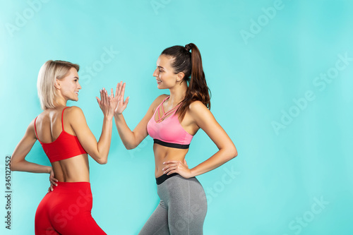 Fototapeta Great workout. Two young and happy sporty girls in sportswear giving each other high five while standing against blue background obraz