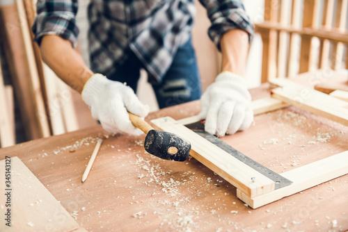 Photo Carpenter Man is Working Timber Woodworking in Carpentry Workshops, Craftsman is Using Rubber Hammer Adjusting Timber Frame for Wooden Furniture in Workshop