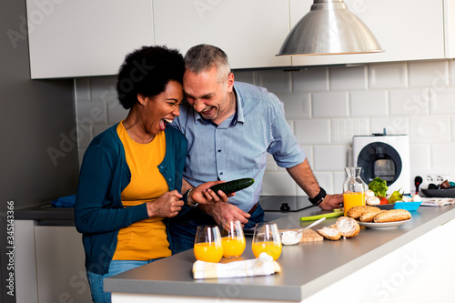 Smiling mixed race couple standing in the kitchen preparing sandwich for breakfast at home Fototapete