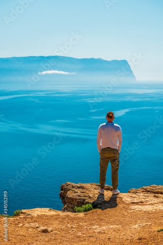 Photo young stylish man Young man stands on The rocky coast looking at blue azure calm sea water in sunny day