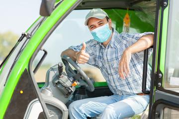 Farmer driving tractor in corn field wearing a mask - coronavirus concept
