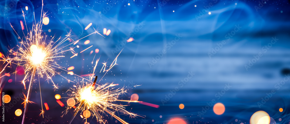 Fototapeta Sparklers With Smoke And Bokeh On Wooden Background - Independence Day Celebration Concept