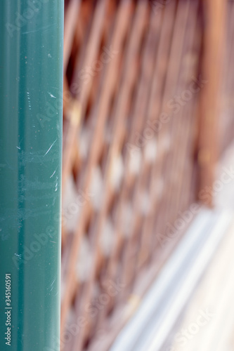 A fragment of a drainpipe on the background of a wooden railing of the verandah Tapéta, Fotótapéta