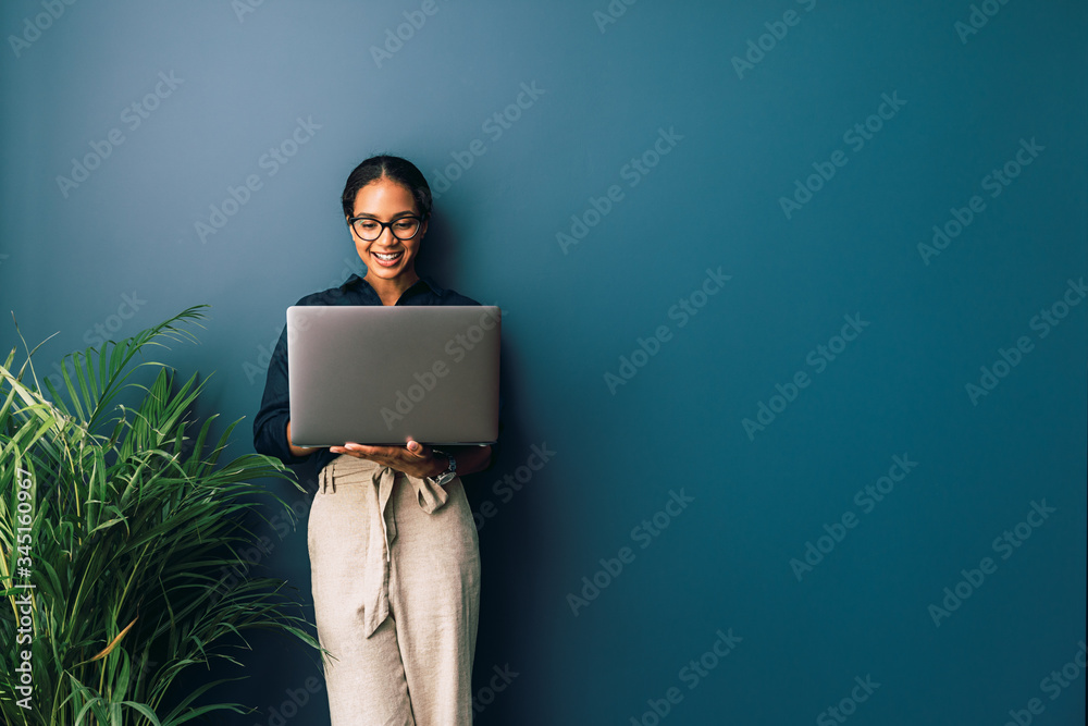Fototapeta Beautiful businesswoman standing at home and holding laptop computer oh hands