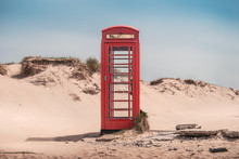 A Vintage Red Telephone Box In The Sand Dunes Of A Deserted Beach Near Sandbanks, Studland, Dorset, England, UK