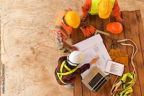 Obraz Top view of architectural engineer working on his blueprints with documents on construction site.focus on shirt engineer.Team of young man and woman engineer and architects working. - fototapety do salonu