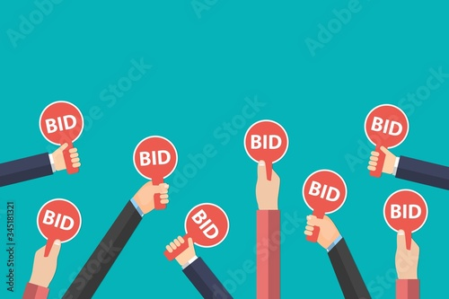 Photo Hands holding auction paddle isolated on blue background