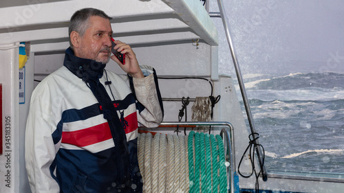 The captain of a small fishing boat is on the phone near the coast Canvas Print