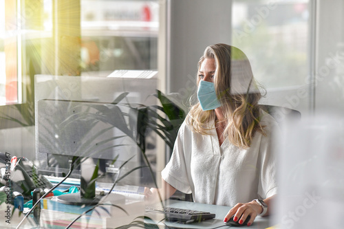 Fotomural Executive woman working at her desk and wearing a protective mask against covid-