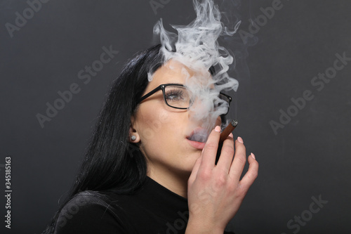 Fotografie, Tablou Attractive european girl with black hair and glasses posing in studio and smoking a cigar on isolated background