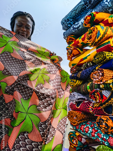Ghana woman looking at various fabrics in Accra market located in Ghana West Africa Canvas Print