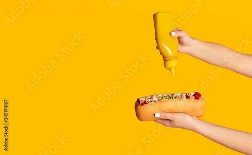 Fotografia, Obraz Unrecognizable woman squeezing mustard onto hot dog against orange background, blank space