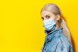 canvas print picture - Studio portrait of young blonde girl with blue eyes, wearing medical face mask against coronavirus. Background of yellow color.