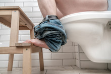 Man Sitting On Toilet Bowl Properly, He Put Feet On A Small Stool In A Squatting Position, During The Defecation. Health Concept.
