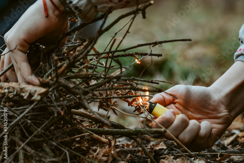 Hands set fire to bonfire in dry forest with lighter or match Wallpaper Mural
