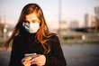 Portrait of sad teenage girl using smart phone wearing protective face medical mask standing outdoors on city street