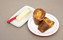 Two Home Baked Popovers On A Blue And Red Trimmed Off-white Plate And A White Butter Dish With A Stick Of Butter And Red-handled Knife Are On A Textured Beige Background.