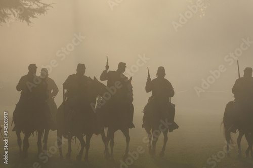 Group of silhouetted Soldiers on Horseback with Guns in the air moving forward i Fototapet
