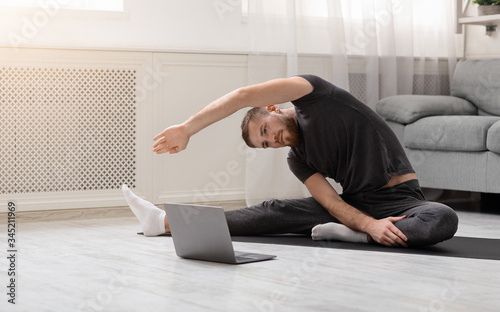 Photo Active man practicing sports training online on laptop