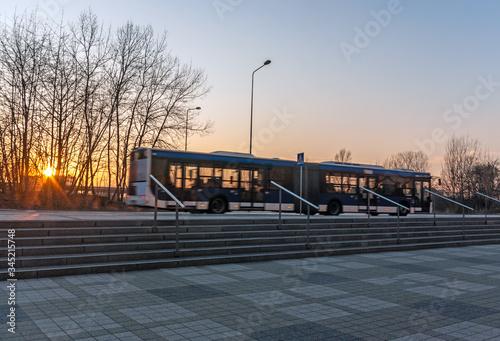 Obraz Biało-niebieski, krakowski autobus miejski podczas zachodu słońca. - fototapety do salonu