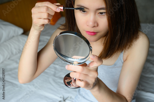 Photo Portrait of young Asian woman applying black mascara on her eyelashes with a wand applicator