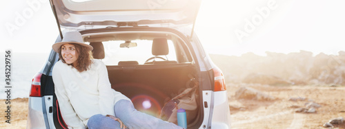Handsome traveling woman sitting in the trunk of a car and resting, chilling stop on the nature. Intentional overexposed and lens flares. Wide screen, panoramic