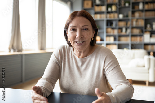Head shot mature woman looking at camera and talking, grandmother chatting with Canvas Print