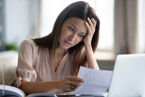 Obraz Unhappy woman touching forehead and holding paper, reading bad negative news in letter, upset young female shocked by unexpected loan debt, bank or job dismissal notification, eviction notice - fototapety do salonu