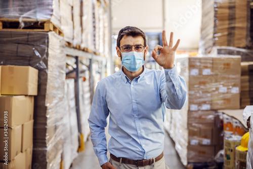 Fototapeta Full length of handsome smiling businessman having phone call with customer while walking in warehouse. obraz