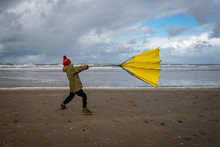 Young Boy Struggling With Large Yellow Umbrella On Beach In Stormy Weather. Winter Beach Scene.