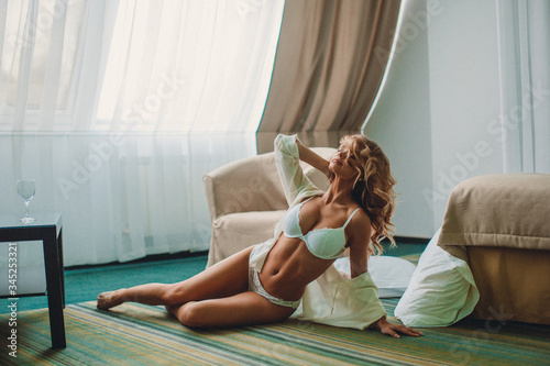 Fototapeta Young beautiful girl with good body shapes in a bright hotel room in beautiful lingerie obraz na płótnie