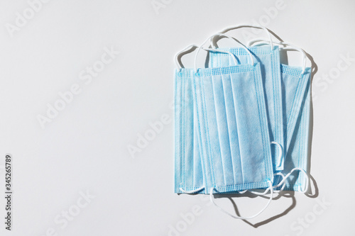 Cuadros en Lienzo Stack of facial medical masks, white background, close up