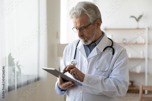 Senior male doctor using digital tablet computer tech providing online healthcare telemedicine ehealth services standing in hospital office Fototapet
