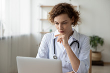 Concentrated Young Female Physician Working On Computer Looking At Laptop Screen Thinking On Problem Solution Concept. Serious Woman Doctor Wearing White Coat Doing Online Research At Workplace.
