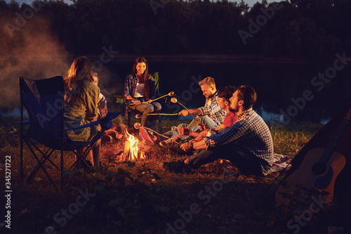 A group of people sitting by the bonfire next to the tent at night in the summer in autumn Wallpaper Mural