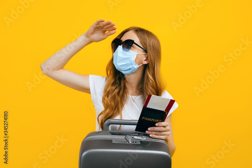 a female tourist in a medical protective mask on her face, with a passport and a Wallpaper Mural