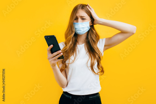 An agitated woman in a protective medical mask looks at the mobile phone screen on a yellow background Wallpaper Mural