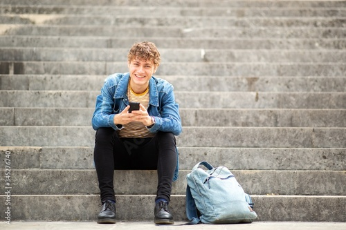 Fotografía Full length smiling young man sitting on steps outside holding cellphone
