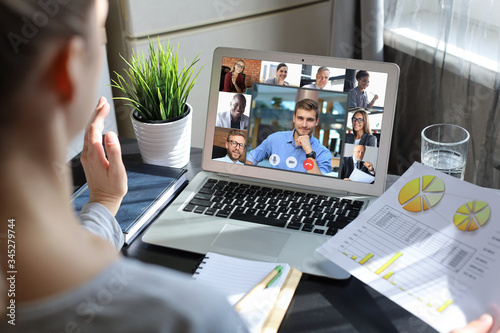 Obraz Business woman talking to her colleagues in video conference. Multiethnic business team working from home using laptop. - fototapety do salonu
