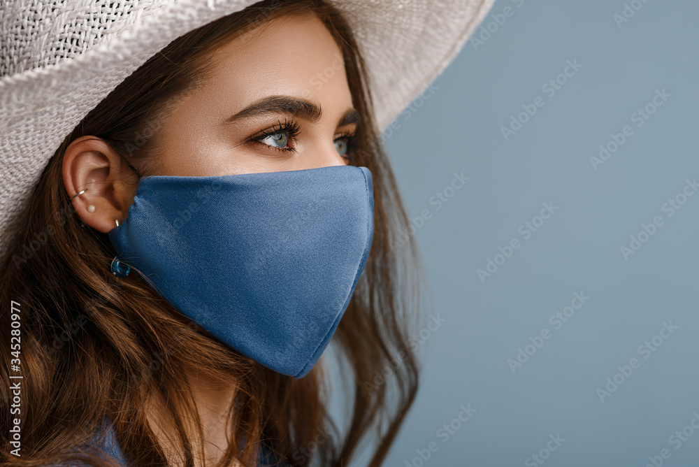 Fototapeta Woman wearing stylish protective face mask, posing on blue background. Trendy Fashion accessory during quarantine of coronavirus pandemic. Close up studio portrait. Copy, empty space for text
