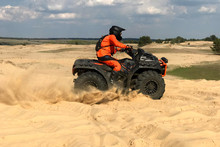 A Man Riding A Quad Bike In Th...