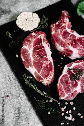 Fototapeta Pork neck on a black board with herbs obraz na płótnie