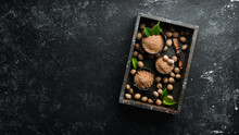 Whole Nutmeg On Black Stone Background. Spices. Free Space For Your Text. Top View.