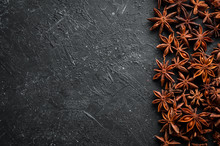 Fresh Organic Asian Anise Stars On Black Stone Background. Badian - Indian Spices. Top View.