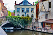 canvas print picture - View of Dijver canal with canal boat, vine covered bridge and traditional buildings in Bruges, Belgium