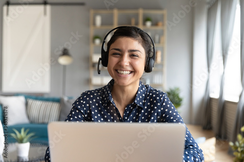 Foto Head shot cheerful smiling pretty hindu ethnic girl sitting at table with computer, wearing headphones with mic, looking at camera