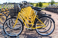Row Of Bicycles Parked. Yellow Bicycles Stand On A Parking For Rent.To Save Energy And Environmentally Friendly. Selective Focus.