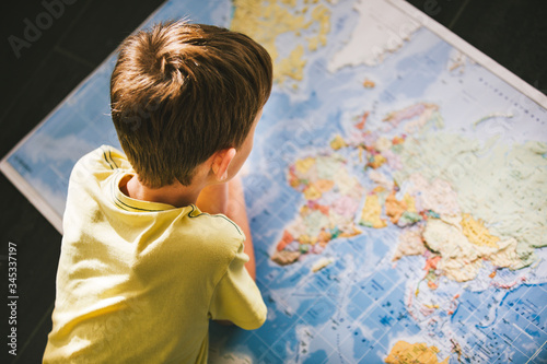 Young boy studying the world map. Dreaming of travel in the times of isolation.